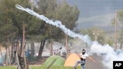 Un migrant renvoie une canette de gaz lacrymogène vers la police macédonienne lors d'une manifestation près du poste-frontière grec d'Idomeni, le 10 avril 2016.