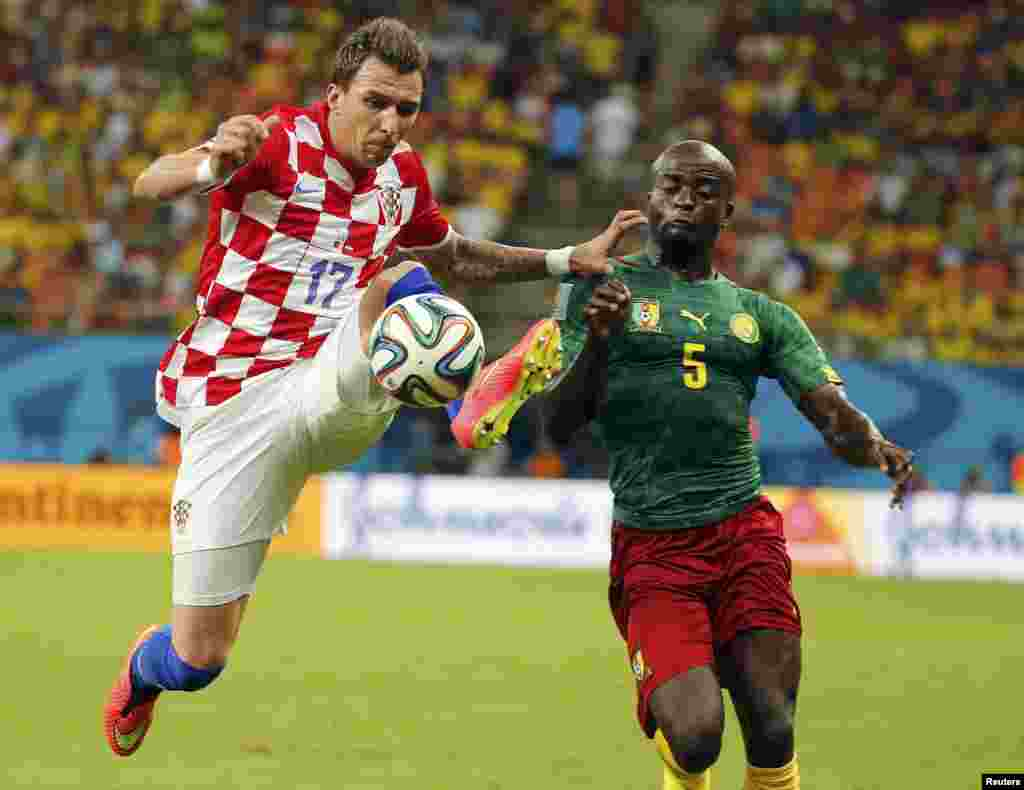Croatia's Mario Mandzukic (L) fights for the ball with Cameroon's Dany Nounkeu during their 2014 World Cup Group A soccer match at the Amazonia arena in Manaus June 18, 2014. REUTERS/Siphiwe Sibeko (BRAZIL - Tags: SOCCER SPORT WORLD CUP TPX IMA