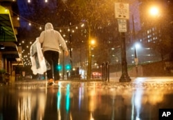 FILE - A person carries his dry cleaning while walking in the rain through midtown Atlanta, Wednesday, Dec. 23, 2015.