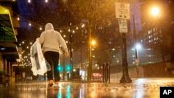一名行人带着干洗的衣服冒雨走在亚特兰大市中城的街头。(2015年12月23日)