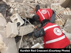 FILE - Kurdish Red Crescent workers search for survivors after an attack in Afrin, January 2018.