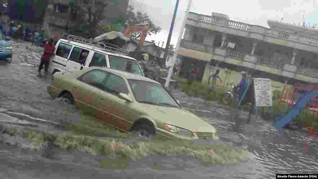 Quasiment impossible de faire les courses sans entrer dans l'eau dans les quartiers avoisinant le stade Général Mathieu Kerekou, à Cotonou, Benin, 8 octobre 2016. VOA/Ginette Fleure Adande
