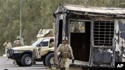 Iraqi army soldiers stand guard near burned trailers at Camp Ashraf north of Baghdad, Iraq, April 8, 2011