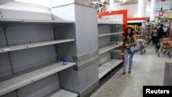 Los venezolanos frecuentemente encuentran los anaqueles vacíos de los supermercados tras hacer largas colas para comprar comida.