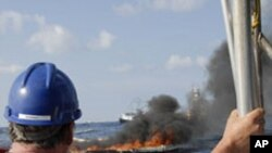 A cleanup worker watches a controlled burn near the Deepwater Horizon oil spill site.