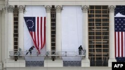 WASHINGTON, DC - JANUARY 13: Workers hang an early version of the American flag on the U.S. Capitol to be used as part of the backdrop to the presidential inauguration for President elect Donald Trump as he prepares to take the reins of power next week on January 13, 2017 in Washington, DC. The inauguration will take place on January 20th when President Barack Obama ends his 8 year run as Americas president. Joe Raedle/Getty Images/AFP
