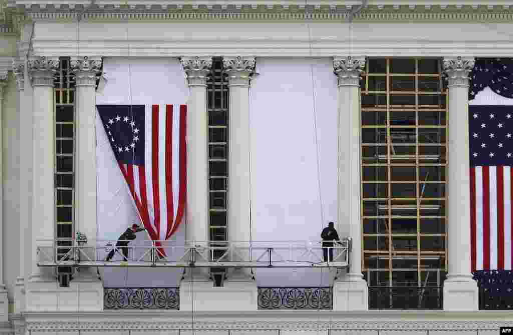 Workers hang an early version of the American flag on the U.S. Capitol to be used during the presidential inauguration for President-elect Donald Trump next Friday.