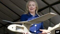 En esta foto la secretaria de Estado de EE.UU., Hillary Clinton, sostiene un drone usado en Uganda para encontrar y destruir explosivos que matan a soldados.