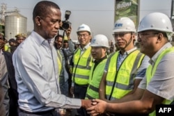FILE - Zambian President Edgar Lungu, left, greets Chinese workers during a walk on a major road in Lusaka, Zambia, Sept. 15, 2018.