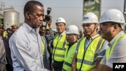 FILE - Zambian President Edgar Lungu, left, greets Chinese workers from Aviation Industry Corporation of China during a walk on a major road in Lusaka, Zambia, Sept. 15, 2018.