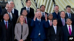 Romanian Foreign Minister Teodor-Viorel Melescanu, center, stands with European Union foreign policy chief Federica Mogherini, second left, and Singapore's Foreign Minister Vivian Balakrishnan, left, during a group photo at an EU ASEAN meeting, Brussels, Monday, Jan. 21, 2019.