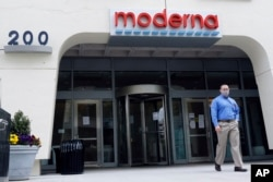 A man stands outside an entrance to a Moderna, Inc., building, Monday, May 18, 2020, in Cambridge, Mass. Moderna announced Monday that an experimental vaccine against the coronavirus showed encouraging results.