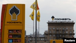 FILE - The logo of Russia's top crude producer Rosneft is seen on a price information board of a gasoline station in Moscow, July 17, 2014.