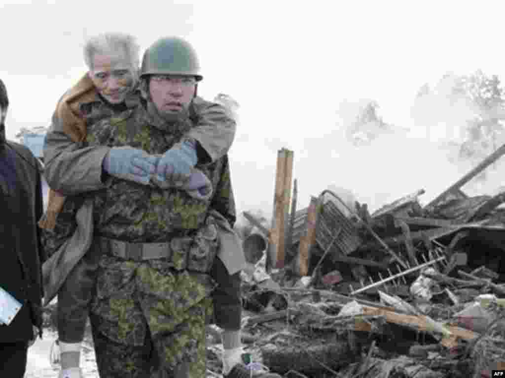 An elderly man is being carried by Self-Defense Force member in the tsunami-torn Natori city, Miyagi Prefecture, northern Japan, Saturday morning, March 12, 2011, one day after strong earthquakes hit the area.