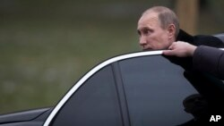 FILE - Russian President Vladimir Putin is seen getting out of his limousine in Moscow, Russia, Feb. 23, 2014.
