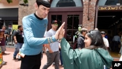 """A Mr. Spock impersonator from Star Trek gives the """"live long and prosper"""" high five to a fan at the 2015 Comic-Con International held at the San Diego Convention Center Friday, July 10, 2015 in San Diego in July 2015. (Photo by Denis Poroy/Invision/AP)"""