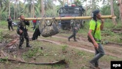 Filipino soldiers carry a recovered body in the town of Jolo, Sulu Island, southern Philippines, April 27, 2016. Authorities are working to confirm whether the headless corpse found on Jolo Island is that of Canadian hostage beheaded on April 25, 2016, by Islamist group Abu Sayyaf.
