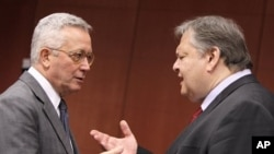 Italian Finance Minister Giulio Tremonti, left, speaks with Greek Finance Minister Evangelos Venizelos during a meeting of eurozone finance ministers at the EU Council building in Brussels, July 11, 2011
