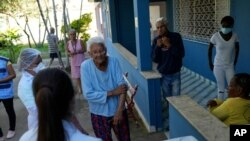 An elderly woman waits to get a dose of the Pfizer COVID-19 vaccine during a booster shot campaign for elderly residents in long-term care institutions, at Casa de Repouso Laco de Ouro nursing home in Rio de Janeiro, Brazil, Sept. 2, 2021.