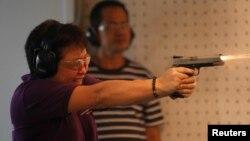 Komisioner biro pajak nasional Filipina Kim Henares berlatih menembak di Manila. (Reuters/Romeo Ranoco)