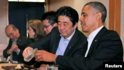 In this April 23, 2014 file photo, Japanese Prime Minister Shinzo Abe (2nd R) pours sake for U.S. President Barack Obama (R) as they have dinner at the Sukiyabashi Jiro sushi restaurant in Tokyo. (REUTERS/Cabinet Public Relations Office/Pool)