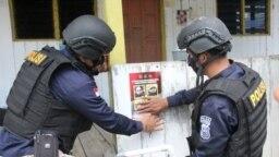 Petugas menempel poster memuat foto dan identitas empat teroris anggota MIT yang masih diburu dalam operasi Madago Raya. Sabtu (25/9/2021). (Foto: Courtesy/Humas Polda Sulteng)