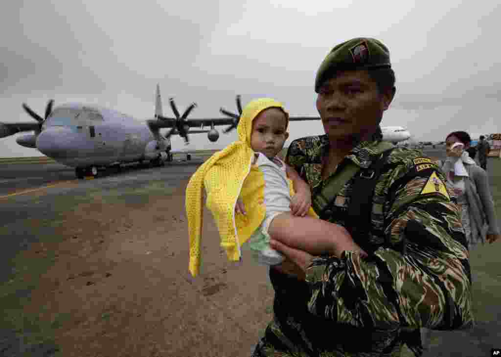 A soldier carries a baby to board a U.S. military transport plane at the damaged Tacloban airport, Tacloban city, Philippines, Nov. 17, 2013.