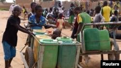 اسکول میں موجود پانی کے نلکوں سے شہری پانی لے کر جا رہے ہیں