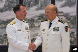 美国海军作战部长理查森和中国海军司令吴胜利在北京的中国海军总部握手(2016年7月18日)