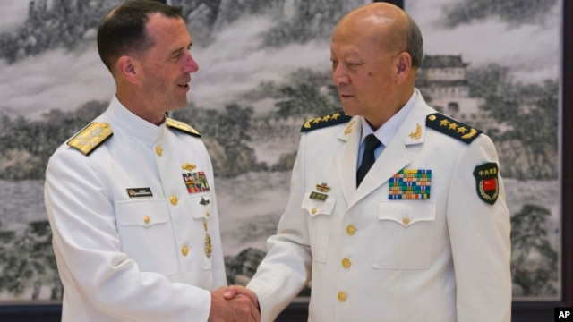 U.S. Chief of Naval Operations Adm. John Richardson (L) and Commander of the Chinese navy, Adm. Wu Shengli shake hands at Chinese Navy Headquarters in Beijing, China, July 18, 2016.