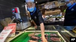 北京一名超市工作人員為牛肉貼上銷售標籤。2020年8月28日圖片。