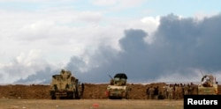 FILE - Iraqi soldiers gather near vehicles as smoke rises from oil wells in the Ajil field east of Tikrit in the Salahuddin province that were set on fire by Islamic State militants in March 2015.