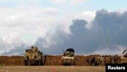 IŞİD'in yaktığı pkuyularından yükselen dumanları seyreden Irak kuvvetleri