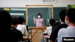 A student makes a presentation behind a plastic sheet to prevent the coronavirus disease infection during an english class at Takanedai Daisan elementary school in Funabashi, east of Tokyo, Japan July 16, 2020. (REUTERS/Kim Kyung-Hoon)