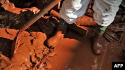 Một người lính Hungary mặc quần áo bảo vệ, dọn dẹp 1 ngôi nhà bị ngập bùn đỏ độc hại ở Hungary, 7/10/2010