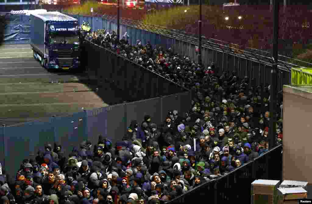 Fans of AS Roma leave the Kuip stadium through a secured corridor after the Europa League soccer match against Feyenoord in Rotterdam, Netherlands, Feb. 26, 2015.