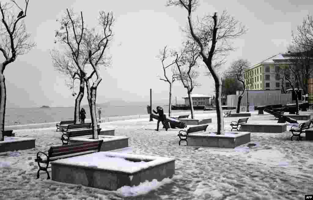 Warga setempat berjalan di Lapangan yang diselimuti salju di kota Istanbul,Turki.