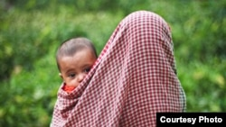 A child in the arms of its mother in Bangladesh.