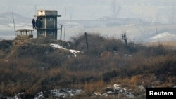 North Korean soldiers watch the South Korean side from a lookout tower at their observation post in the demilitarized zone (DMZ) separating the two Koreas, December 28, 2011.
