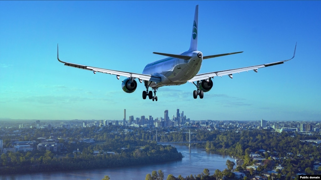 A commercial aircraft prepares to land over a city.