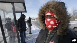 Protegiéndose del frio en una parada de autobús, en Chicago.