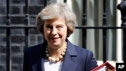 FILE- Britain's Prime Minister Theresa May leaves 10 Downing street in London, July 20, 2016. On her first visit to China as Britain's prime minister, Theresa May will try to reassure Beijing that she wants to strengthen ties despite her delay on a decision over whether to approve a Chinese-backed nuclear power plant in southwestern England.