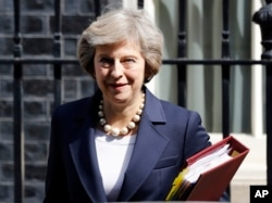 FILE- Britain's Prime Minister Theresa May leaves 10 Downing street in London, July 20, 2016. On her first visit to China as Britain's prime minister, Theresa May will try to reassure Beijing that she wants to strengthen ties despite her delay on a decis