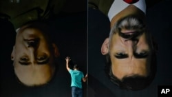 A man sets up upside down giant paintings of late Spanish dictator Francisco Franco, left, and Spanish King Felipe VI ahead of a protest in support of Catalonia's independence movement, in Bilbao, northern Spain, Oct. 15, 2019.