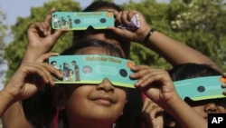 Indian children use cardboard eclipse glasses as they prepare to watch the transit of Venus in Allahabad, India, June 5, 2012.