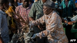 Tanzanian President John Magufuli joins a clean-up event outside the State House in Dar es Salaam on Dec. 9, 2015. Magufuli cancelled Independence Day celebrations and ordered a national day of clean-up instead.