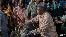FILE - Tanzanian President John Magufuli joins a cleanup event outside the State House in Dar es Salaam on Dec. 9, 2015. Magufuli canceled Independence Day celebrations and ordered a national day of cleanup instead.