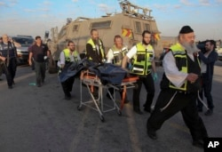 Israeli emergency services evacuate the body of a Palestinian from the scene of an attack near the West Bank Gush Etzion settlements, Nov. 22, 2015.