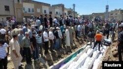 La gente se reúne alrededor de los cádaveres de las víctimas de un bombardeo de las fuerzas sirias en Houla, en el que murieron 108 personas. Decenas más habrían muerto este lunes en nuevos ataques.