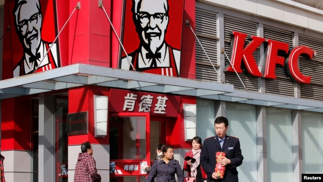 FILE - A man holds instant noodle packs in front of a KFC restaurant in Beijing.